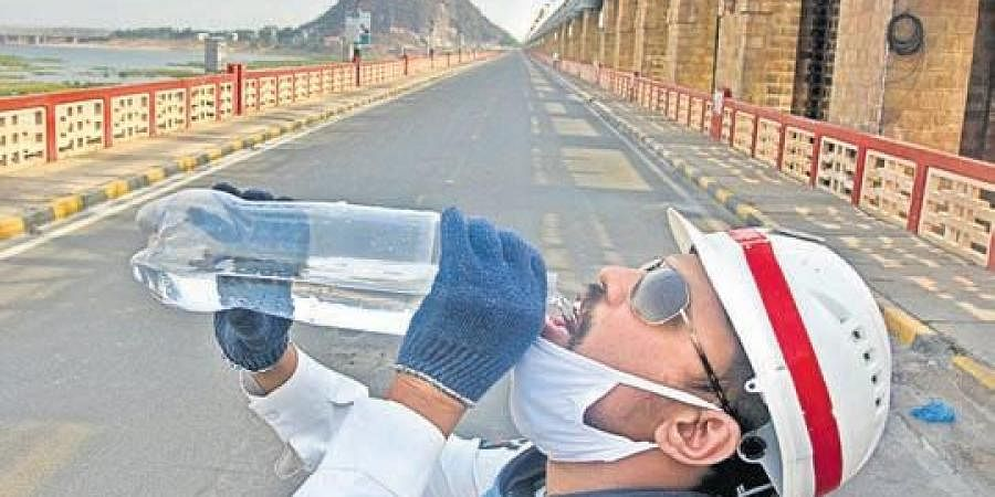 A traffic constable drinking water to beat the heat at Prakasam Barrage  in Vijayawada on Thursday. (Photo | EPS/ I P Ravindra Babu)