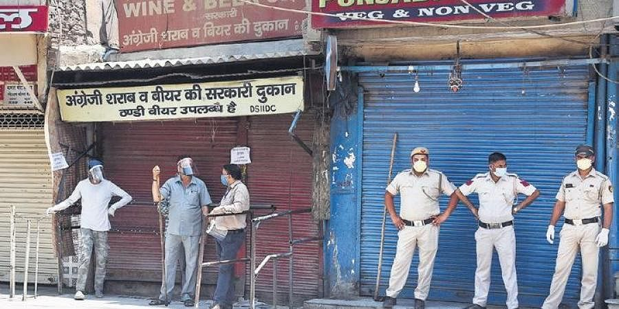Policemen stand guard outside a wine shop after sale of liquor was permitted