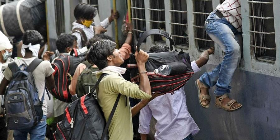 Migrant boards a train at Danapur station to reach their native places, during the ongoing COVID-19 nationwide lockdown in Patna