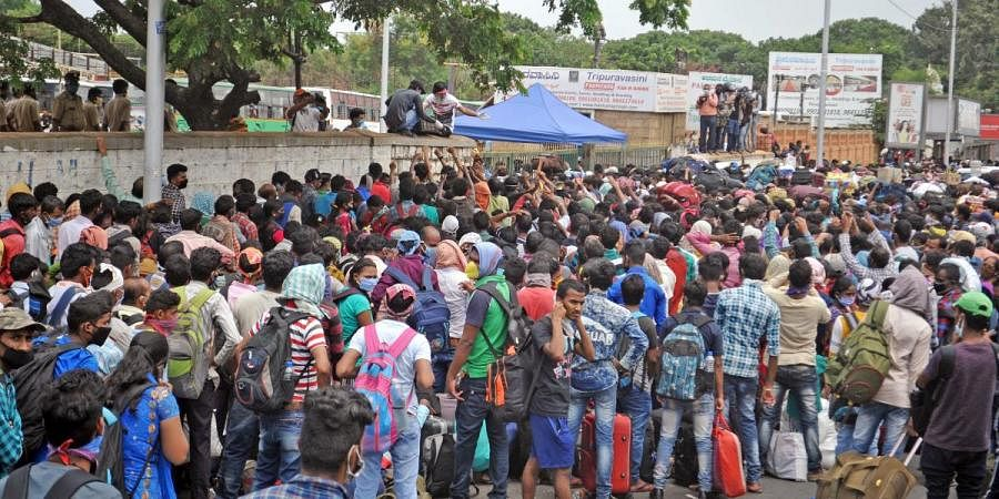 Water bottles being given to migrants from North-East who gathered in huge number at Palace Grounds in Bengaluru to register their travel in Shramik Special trains