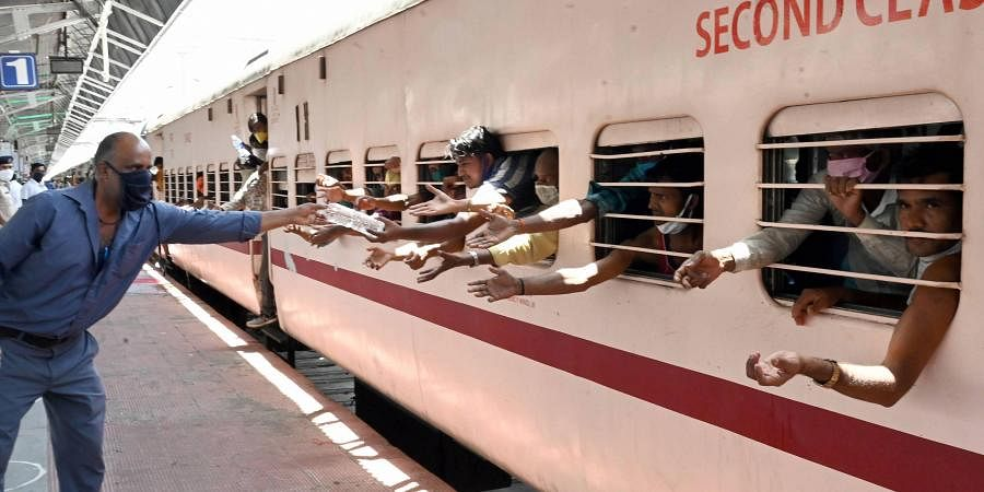 A railway employee provides water bottles to migrants sitting in a train to reach their native places during the ongoing COVID-19 lockdown in Jabalpur. (Photo | PTI)