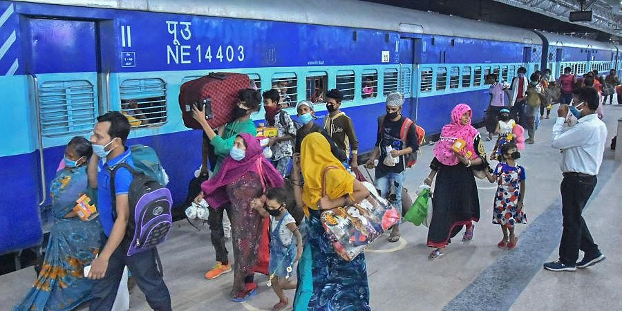 Migrants from West Bengal walk to board a train at Mathura junction during the ongoing COVID-19 nationwide lockdown in Mathura