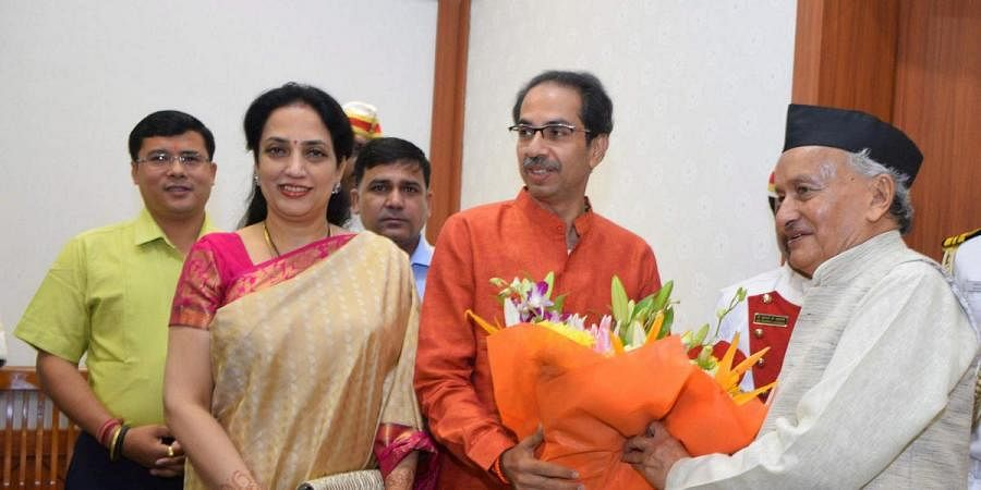 Maharashtra governor BS Koshyari receives a bouquet from CM Uddhav Thackeray and his wife Rashmi Thackeray at Raj Bhavan