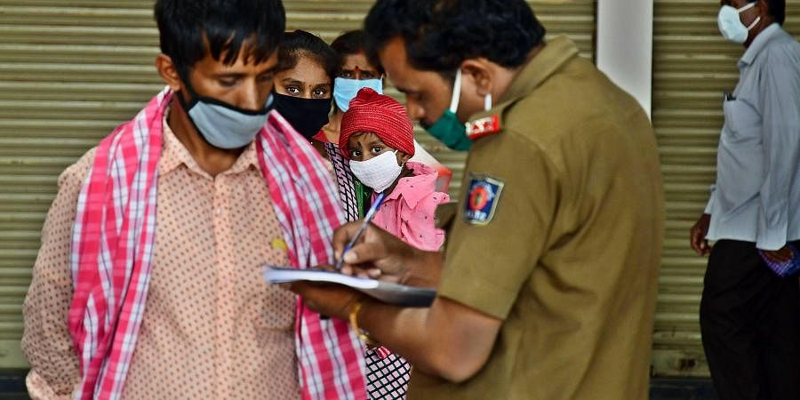Karnataka State Road Transport Corporation officials collect details of passengers arriving at Kempegowda Bus Station, in Bengaluru