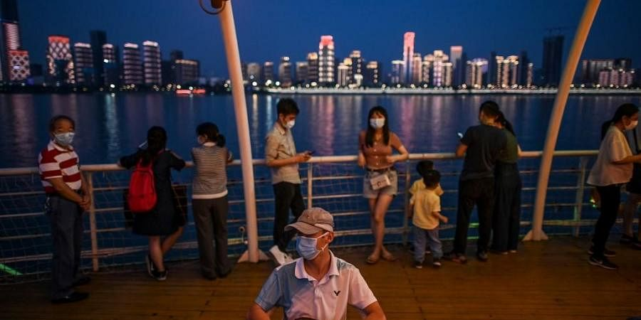 People wearing facemasks are seen on a tourist ship that sail in Yangtze River in Wuhan. (Photo | AFP)