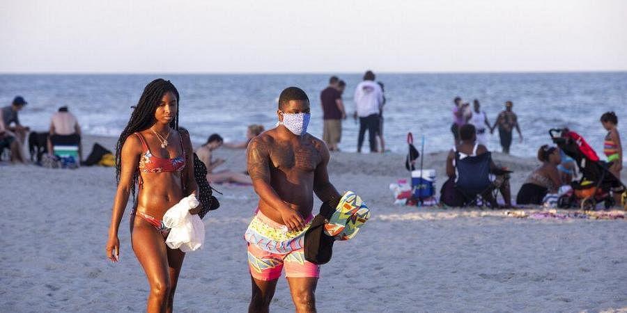 Sunbathers catch the last rays of evening light, amid the coronavirus pandemic. (Photo | AP)