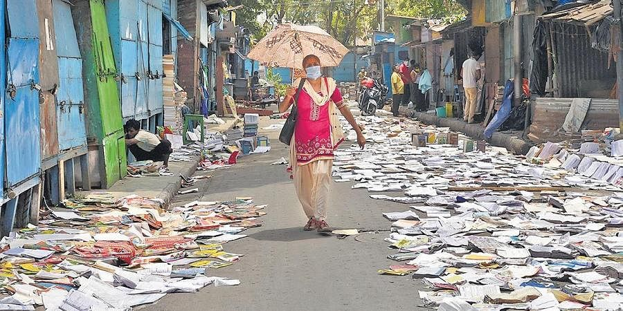A woman walks past books kept on a road to dry after Cyclone Amphan, in Kolkata on Saturday