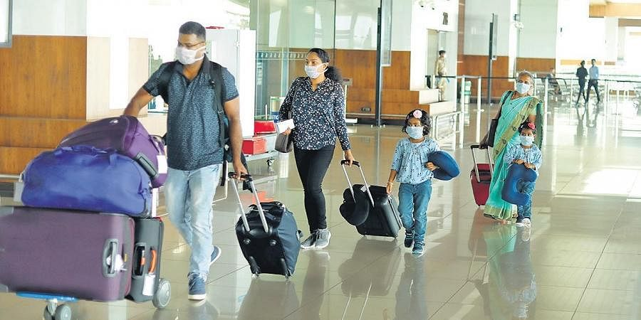 A family reaches Kochi airport wearing safety masks on Sunday