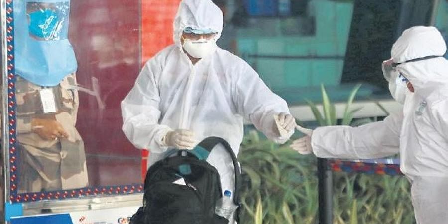 An air passenger wearing PPE suit arrives at IGI Airport in Delhi as domestic flights resumed on Monday