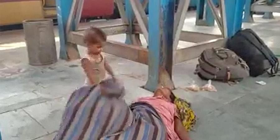 The toddler is seen pulling the shroud covering his mother