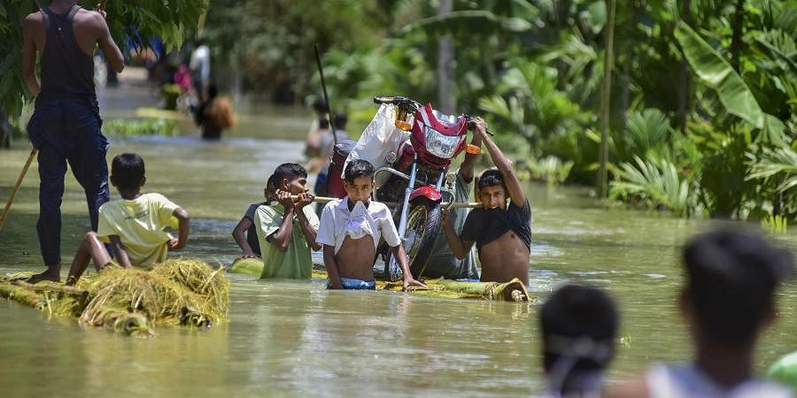 Villagers carry a bike on a banana raft in flood-hit locality of Doboka in Hojai district of Assam.