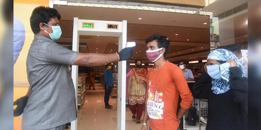 A customer at a garment showroom in Vijayawada being screened