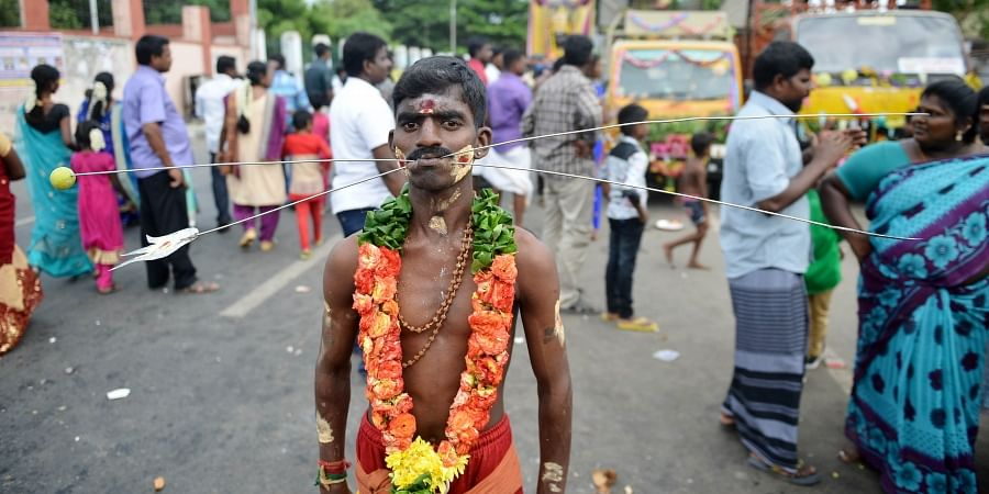 A Hindu devotee with his body pierced with skewers and  walk through a road as he takes part in a religious procession during Aadi festival at elephant gate road, in Chennai.