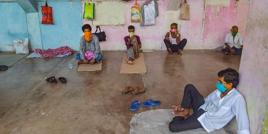 Migrant workers and homeless people rest at a temporary camp set up on the premises of a stadium during ongoing COVID-19 lockdown in Thane
