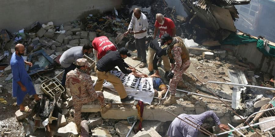 Volunteers cover the dead body of a plane crash victim at the site of the crash in Karachi, Pakistan.