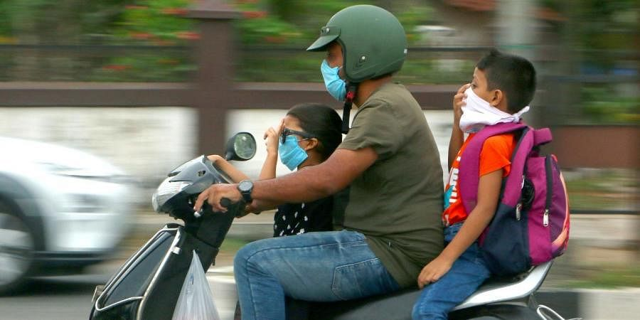 A family riding through the city in Kozhikode with masks on.