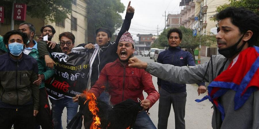 In this Monday, May 11, 2020, file photo, Nepalese students shout slogans during a protest against the Indian government inaugurating a new road through a disputed territory between India and Nepal, in Kathmandu, Nepal.