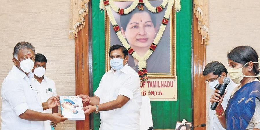 Chief Minister Edappadi K Palaniswami handing over the first copy of 'Comprehensive Guidelines Covid-19' book, brought out by Tamil Nadu Health and Family Welfare Department, to Deputy Chief Minister O Panneerselvam at the Secretariat on Saturday