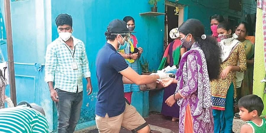 Volunteers distribute sanitary napkins to daily wage and migrant workers