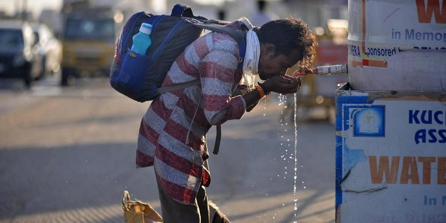 A stranded migrant worker quenches his thirst from a water booth outside Central Railway Station. (Photo| EPS/ Debadatta Mallick)