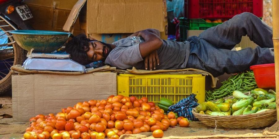 A vendor taking a nap at his vegetable stall during lockdown in Bhubaneswar