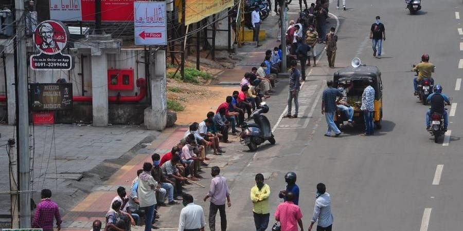 People waiting in front of liquor shops  in Visakhapatnam on Monday.