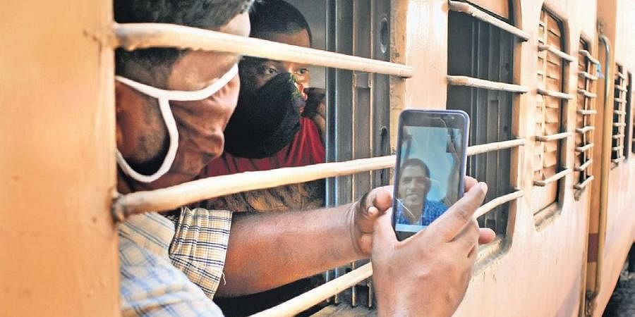 A migrant labourer video calling his brother, who is also in Kozhikode and was not able to board the train, after he got a seat in the train from Kozhikode railway station which will take him to Bihar.