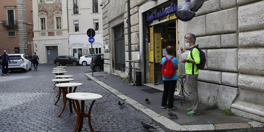 #A customer enjoys a pastry outside a bar in Rome, as bars reopened but only for take away.