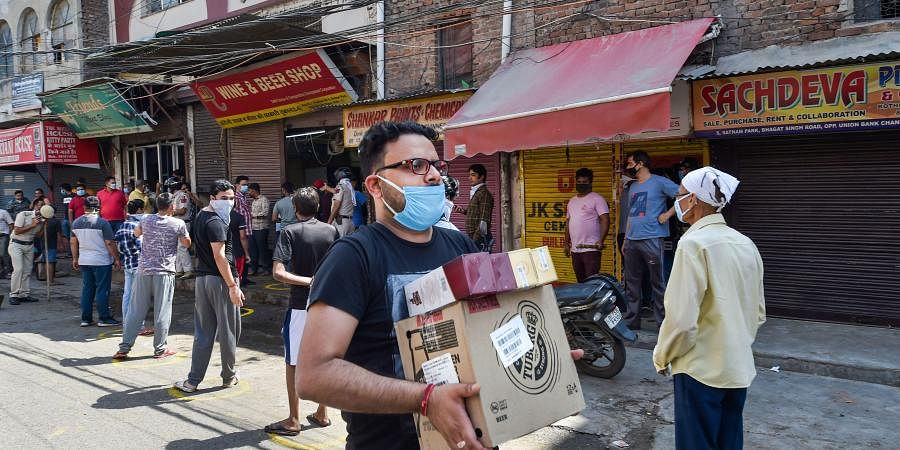 A customer carries alcohol after purchasing from a wine shop during the ongoing COVID-19 nationwide lockdown at Chander Nagar in East Delhi. (Photo | PTI)