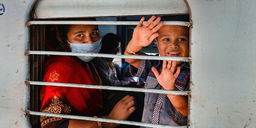 Migrant workers and pilgrims wave as they board a train to their native places during the ongoing COVID-19 nationwide lockdown. (Photo | PTI)