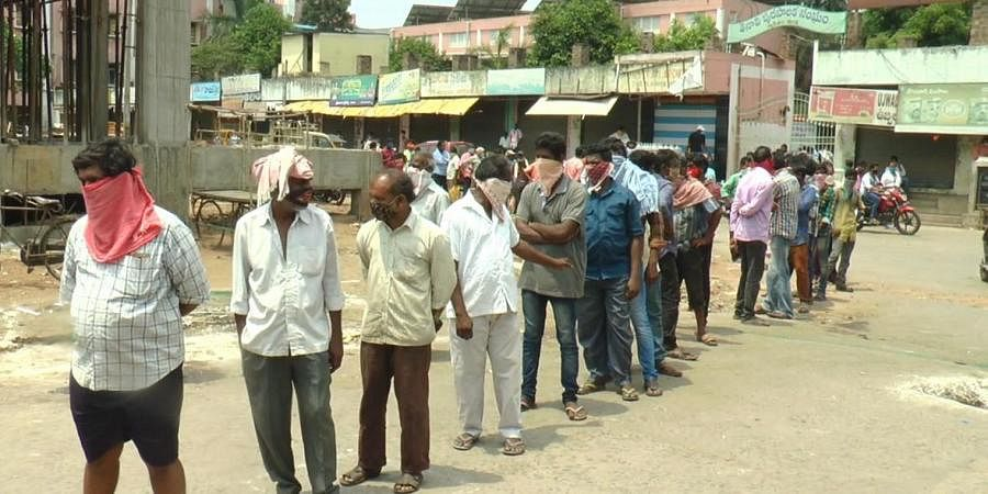 The large number of people thronged to purchase liquor bottles at Tenali in Guntur district on Monday.