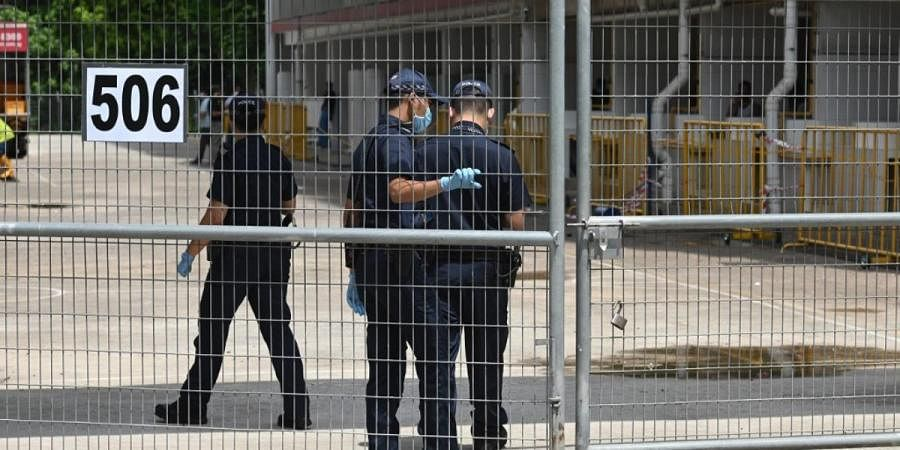 Police officers, wearing face mask enter the gate of a dormitory compound for foreign workers placed under quarantine to battle the spread of COVID-19 in Singapore