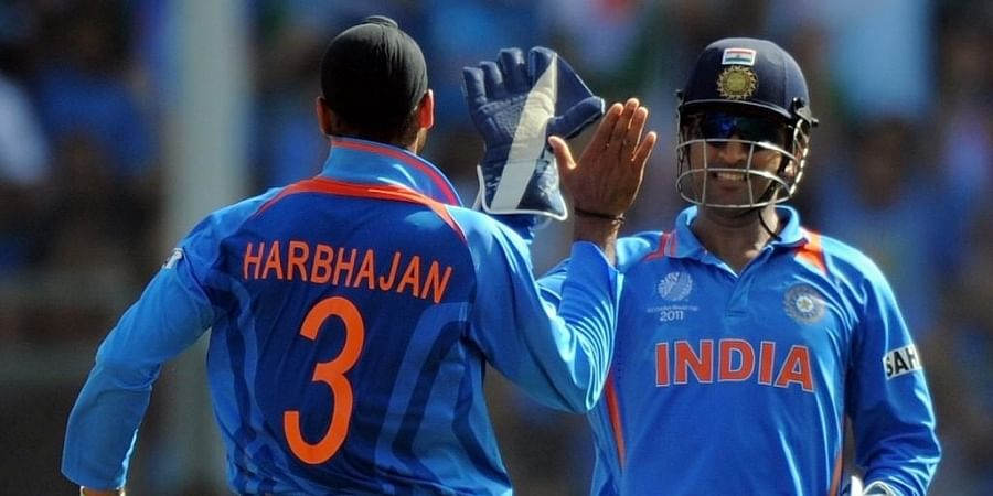 Mahendra Singh Dhoni (R) celebrates with Indian off-spinner Harbhajan Singh. (Photo | AFP)