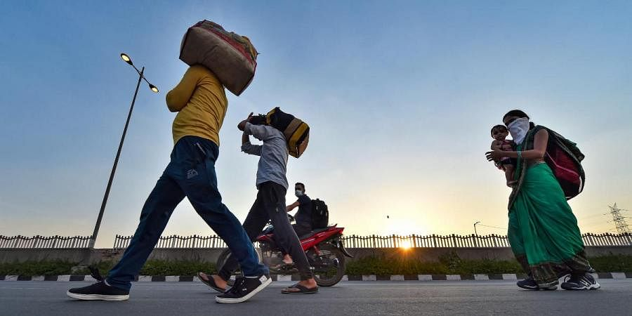 Migrant workers along with their family members walk along the Delhi-UP border road during the ongoing COVID-19 nationwide lockdown, in East Delhi
