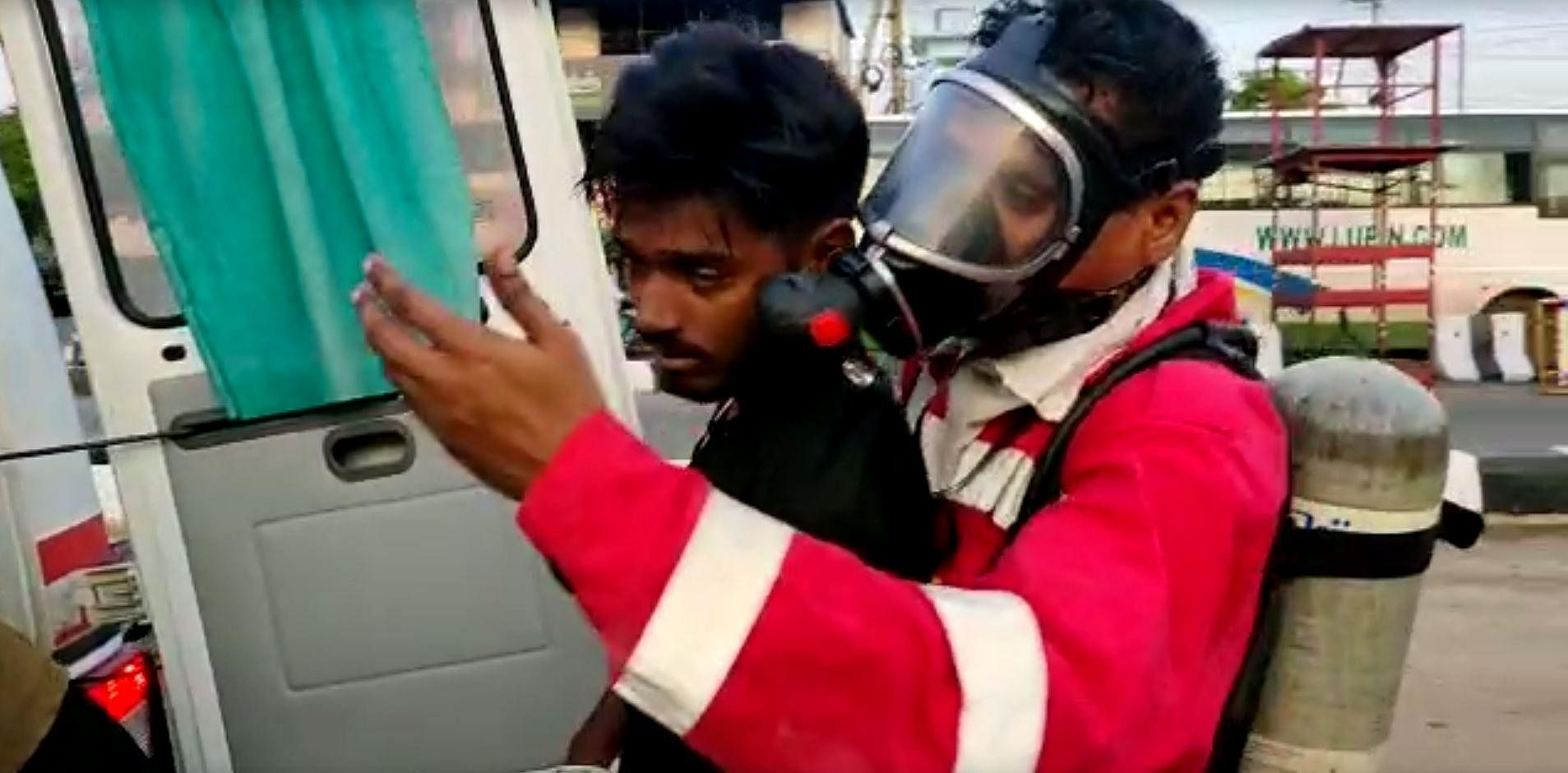 A rescue worker carries an unconscious youth after a major chemical gas leakage at LG Polymers industry near Visakhapatnam