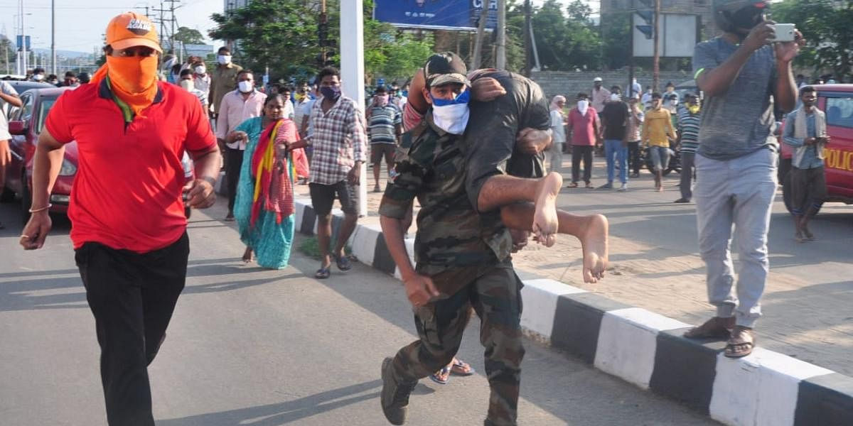 A relief worker carries an unconscious child on his shoulders as he rushes towards a nearby hospital after a gas leak from LG Polymers plant near Visakhapatnam