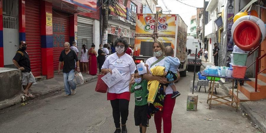 Residents of Paraisopolis slum walk home after attending a health workshop on how to stay safe amid the new coronavirus pandemic in Sao Paulo, Brazil, Wednesday, May 6, 2020.