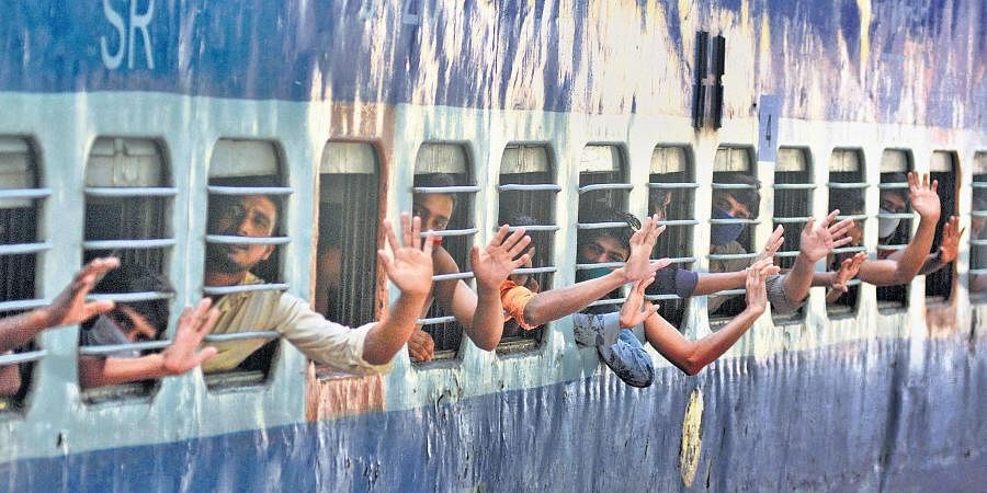 Migrant workers leaving for their home bidding adieu from the railway station ahead of the train's departure
