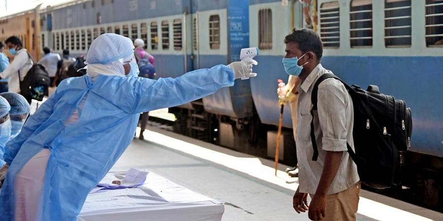 Migrants undergo thermal screening after arriving from Bengaluru by a special train at Danapur Railway Station during the ongoing COVID-19 lockdown, in Patna