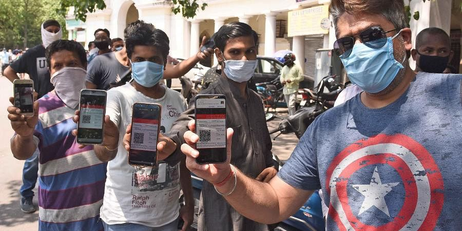 People showing their e-token to purchase liquor during ongoing COVID-19 nationwide lockdown at Gole Market in New Delhi