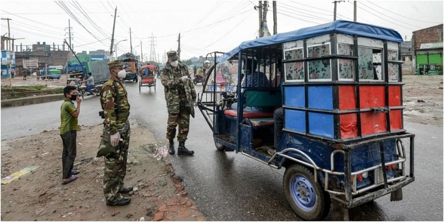 Security personnel stop a motorist at a checkpoint along a road during a government-imposed lockdown as a preventive measure against the COVID-19 coronavirus, in Dhaka on May 1, 2020.