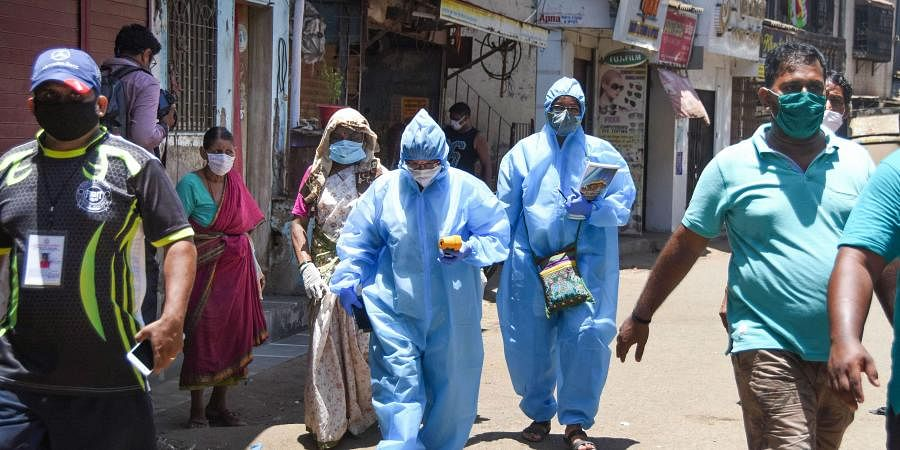 Health workers during a house-to-house health survey at Koliwada after detection of COVID-19 positive cases during the nationwide lockdown at Dharavi in Mumbai on May 8 2020.