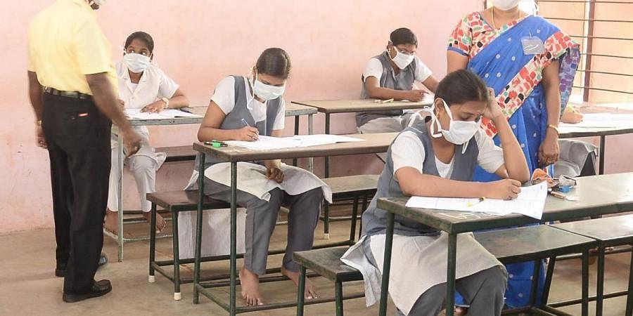 Students are seen writing thePlusoneexaminations wearing masks at MC School in Madurai
