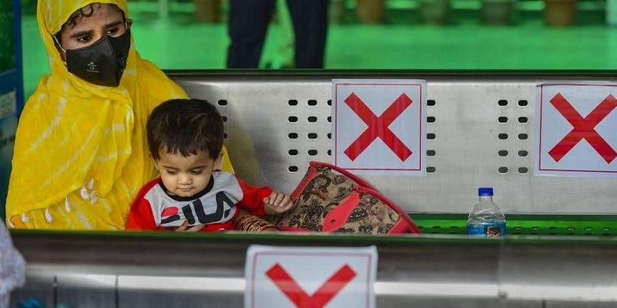 A passenger wearing mask waits along with her son for the arrival of a train at the Nizamuddin Railway Station as Indian Railways resumed operations of 200 passenger trains in