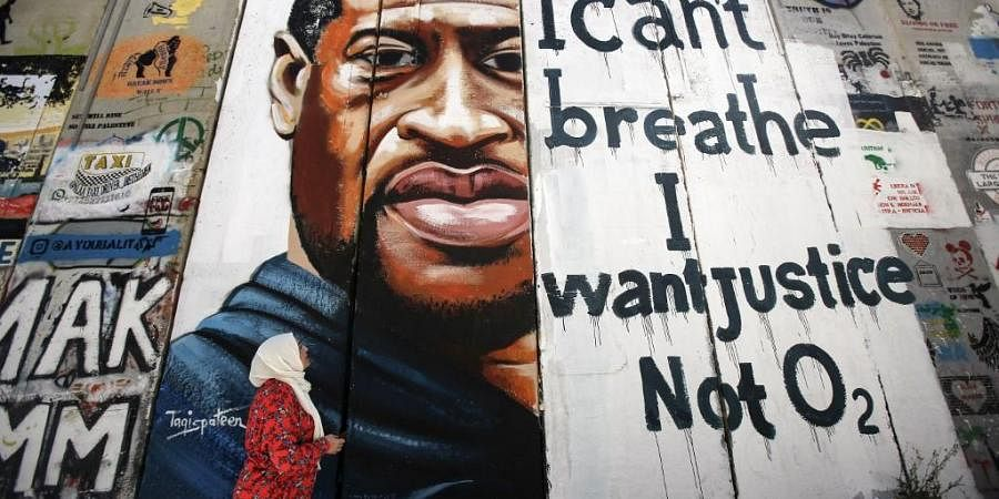 A woman looks at a mural showing the face of George Floyd, an unarmed black man who was killed by Minneapolis police. (Photo |AFP)