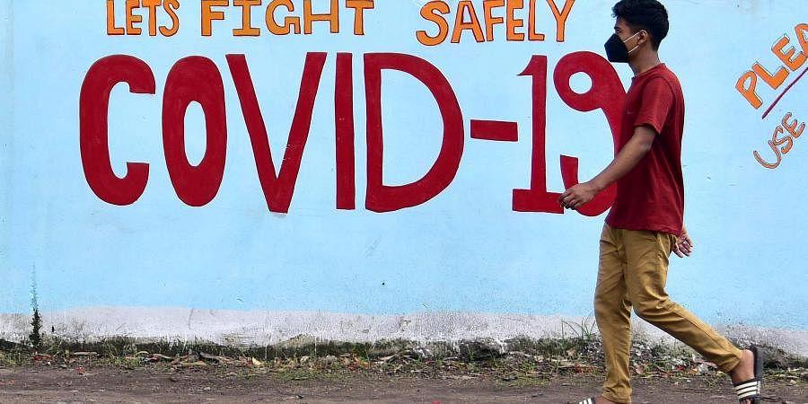 A boy passes by a coronavirus graffiti. (Photo| ANI)