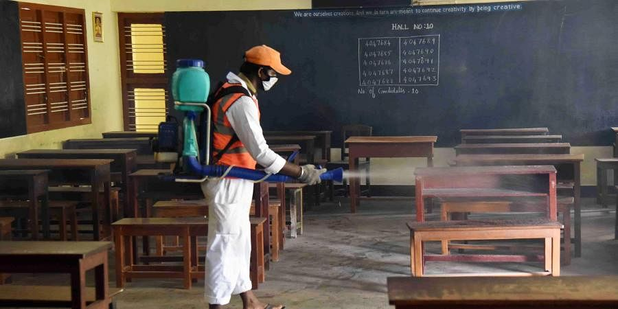 A cleanliness worker disinfects a Plus Two exam paper evaluation centre at a school in Tirunelveli