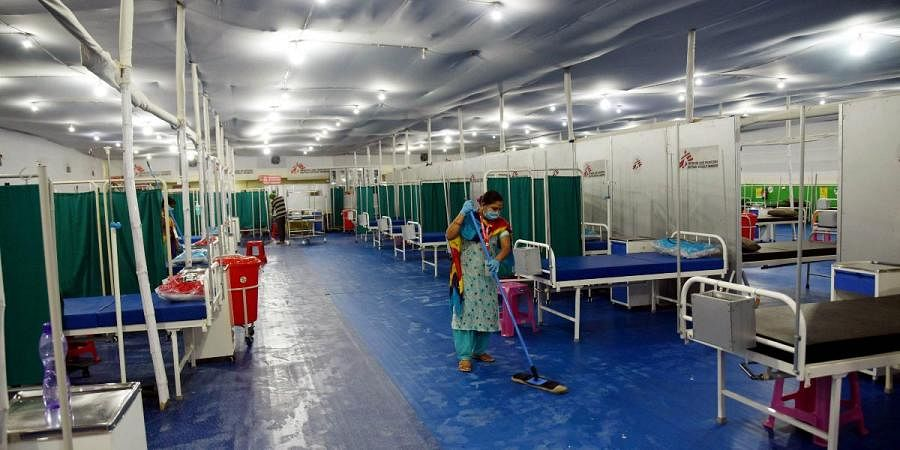 A worker cleans at makeshift 100-bed COVID-19 treatment center set up inside Patliputra sports complex, in Patna