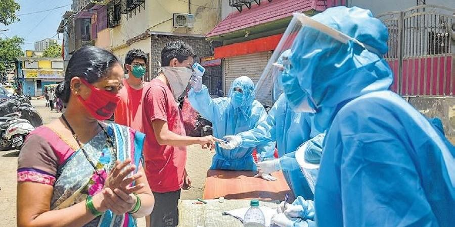 Volunteers carry out thermal tests of residents at Dharavi in Mumbai