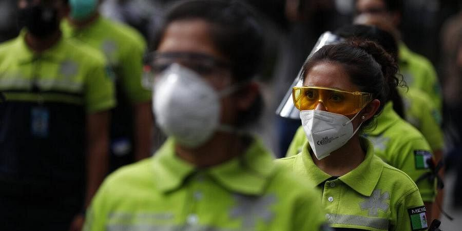 Paramedics prepare to mark a moment of silence in honor of their colleagues who have been killed by COVID-19, at the Angel of Independence monument in Mexico City, Saturday, May 30, 2020.